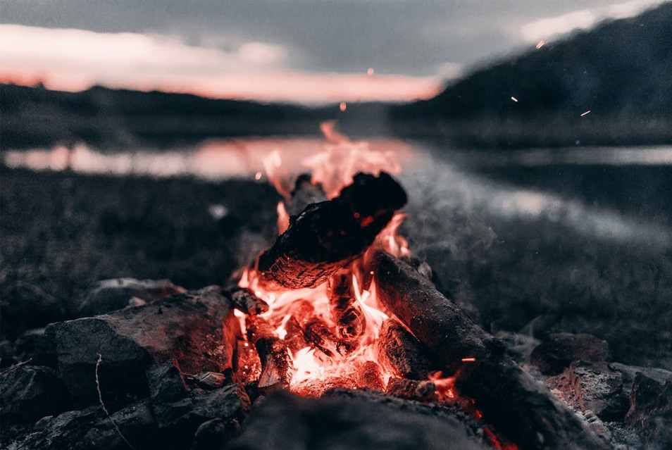 Bright Bonfire Near Lake And Mountains At Night